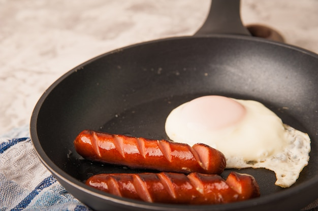 Close-up of sausages and fried eggs. sausages in a pan and place for text.