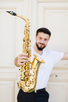 Close up saxophone held by defocused man