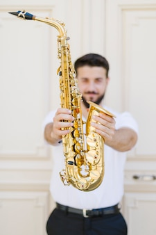 Close up saxophone held by musician