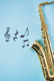 Close-up of saxophones with musical notes on blue background
