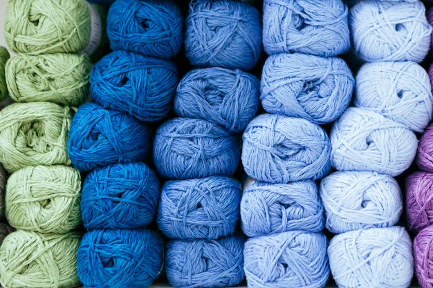 Close up of a scale of blue wool yarns organized by color and storage on a shelf