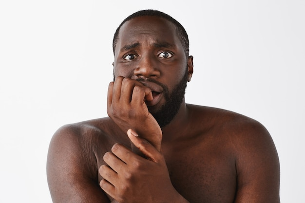 Close-up of scared young guy posing against the white wall