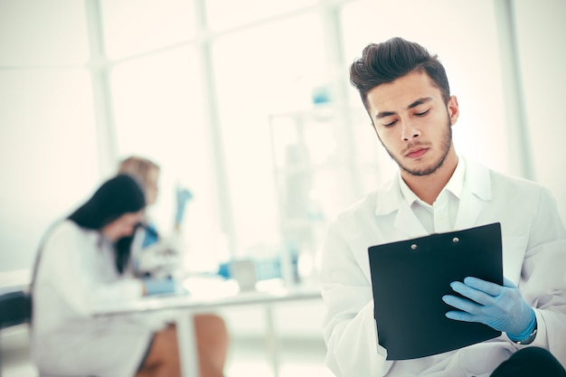 Close up. a scientist doing writes the results of an experiment to a laboratory journal . photo with copy space
