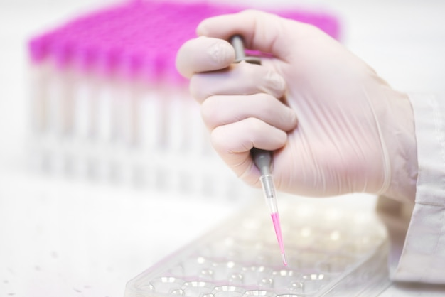 Close up scientist hand holding pipette making biochemistry test at laboratory