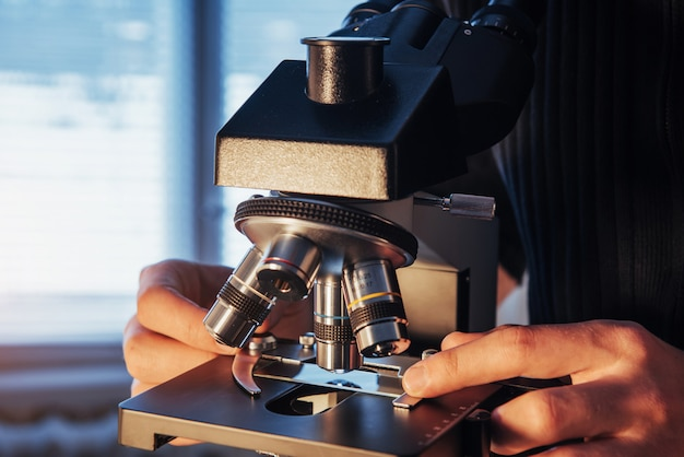 Close-up of scientist hands with microscope, examining samples.
