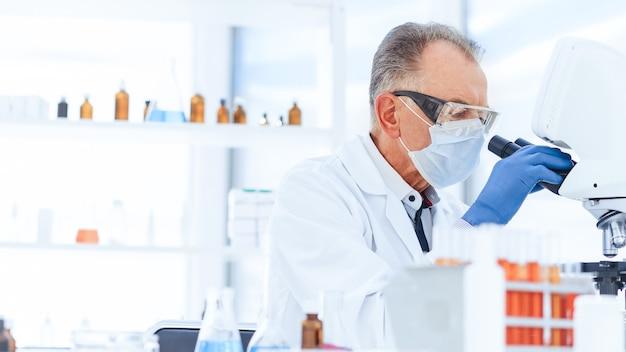 Закройте вверх. ученый в защитной маске проводит исследования в лаборатории. наука и охрана здоровья.