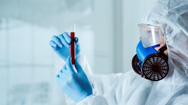 확대. 전체 보호 장비를 입은 과학자가 시험관을 본다.
