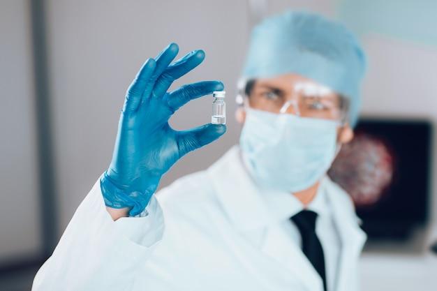 확대. 새로운 백신으로 캡슐을보고있는 과학자. 과학과 건강.
