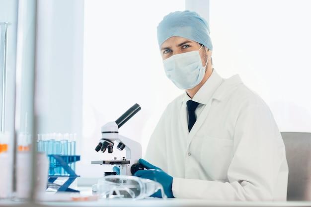 확대. 현미경의 접안 렌즈를 조사하는 과학자