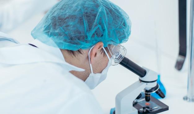 Закройте вверх. ученый смотрит в микроскоп. фото с копией пространства.