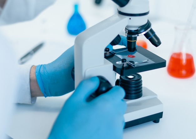 Закройте вверх. ученый настраивает свой микроскоп на работу. фото с копировальным пространством.