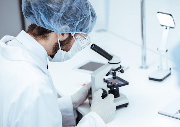 확대. 실험실에서 현미경을 사용하는 과학자. 복사 공간이 있는 사진.