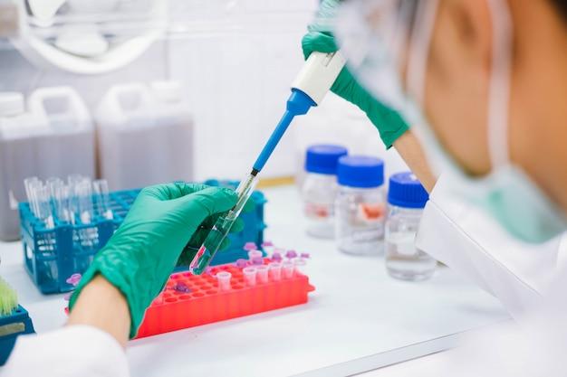 Biosafetyキャビネットでのpcrテストのために、マイクロ遠心チューブにサンプルを移すピペットを使用して科学者を閉じます。