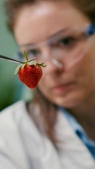 Primo piano di una donna scienziata che guarda una fragola organica usando pinzette mediche per esperimenti di biologia dei frutti