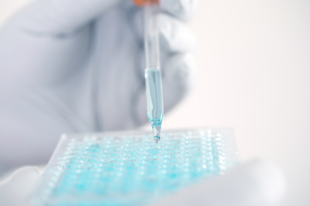 Close up a scientist working in laboratory to analyze blue extracted of dna  molecules
