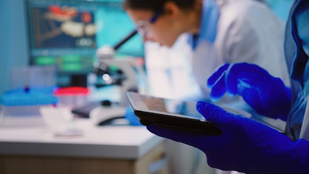 Close up of scientist writing on tablet while team of biologists doing biological researches under microscope in backgorund late at night