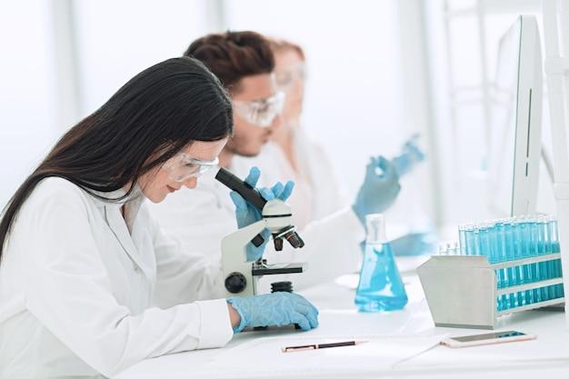 Закройте вверх. ученые и лабораторные работники, сидя за лабораторным столом. наука и здоровье