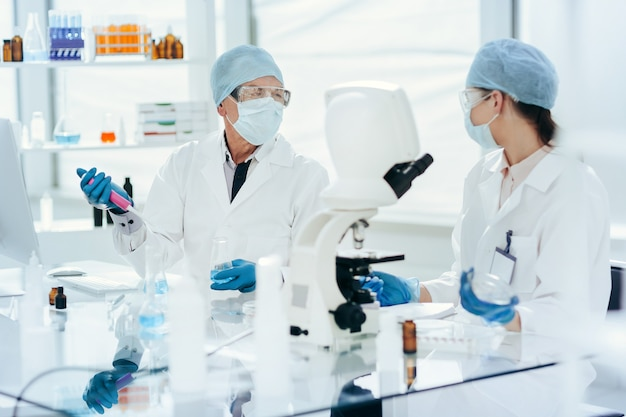 閉じる。研究室で彼らの研究について議論している科学者。