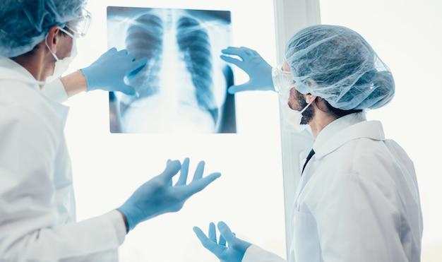 閉じる。肺のx線写真を見ている保護マスクの科学者。ヘルスケアの概念。