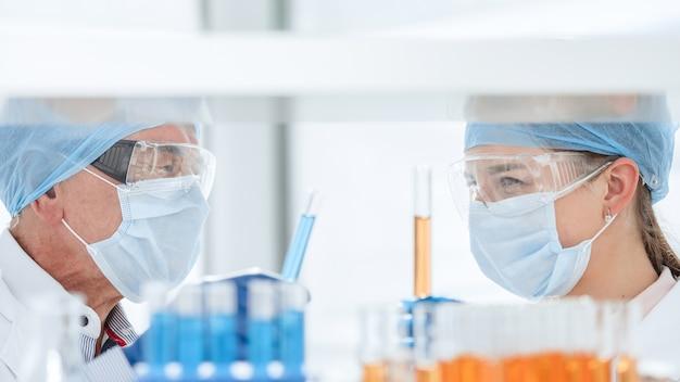 확대. 생화학 실험실에서 시험관을 가진 과학자들.