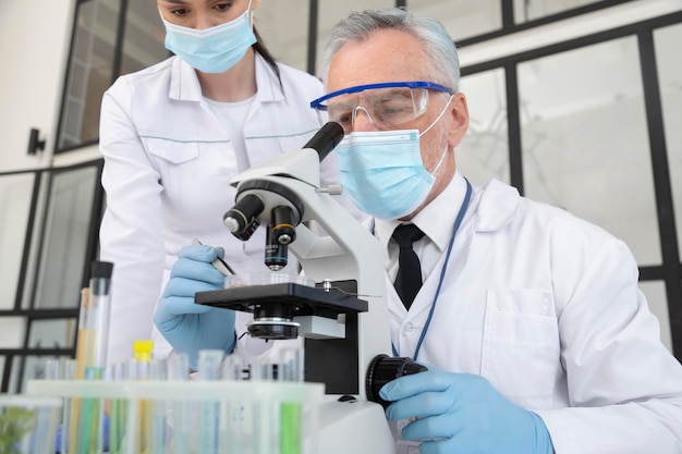 현미경으로 작업하는 과학자를 닫습니다