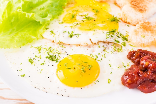 Close-up of scrambled eggs, fried bread, ketchup and lettuce leaves on a plate