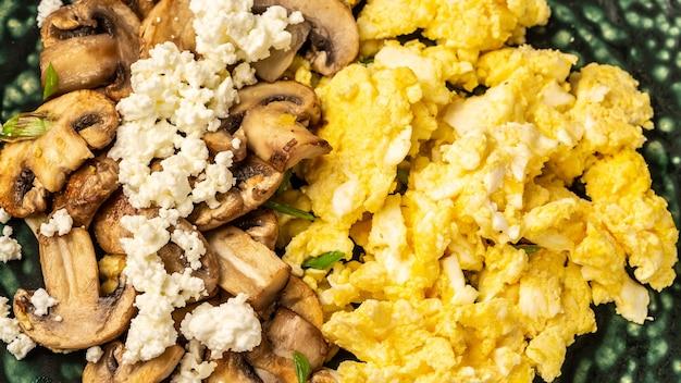 Close up of scrambled eggs with champignon mushrooms,