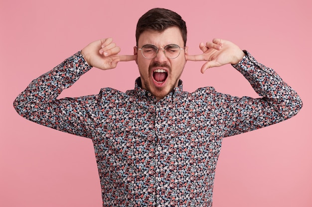 Close up of screaming shouting angry young bearded man dressed in colorful shirt, keeps closed eyes, two fingers close his ears, showing gesture of deafness, ignores someone, over pink wall