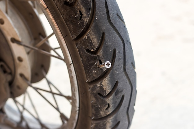 Close up of screw nail puncturing motorcycle tire or bicycle tire