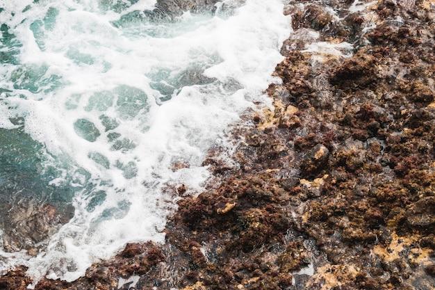 Close-up sea touching rocky shore