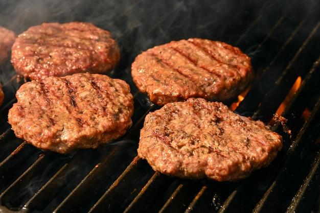 Крупным планом обжигающие и копченые гамбургеры из говядины или свинины для барбекю для гамбургеров на гриле с чугунной металлической решеткой, высокий угол обзора