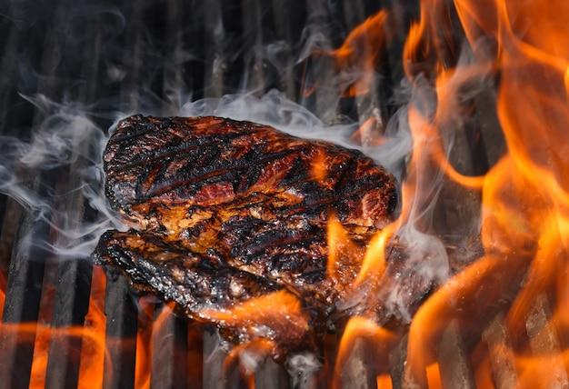 주철 금속 화격자가 있는 야외 그릴에 구운 연기가 나는 ribeye 쇠고기 스테이크를 닫습니다