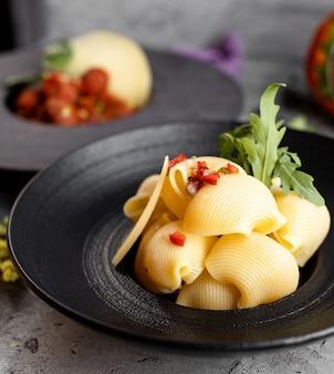 Close up of seashells pasta garnished with arugula tomato and onion cubes
