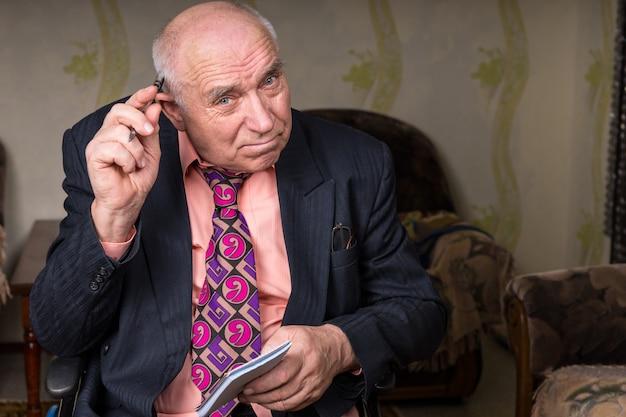 Закройте сидящего старого бизнесмена, держащего небольшие заметки, почесывая лысую голову ручкой и глядя прямо в камеру.