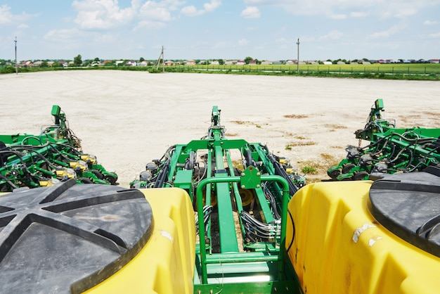 Close up of seeder attached to tractor in field.