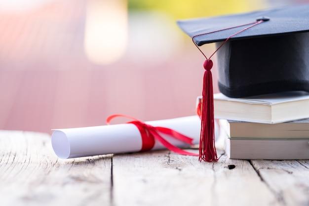 Крупным планом выборочный фокус выпускной кепки или ступки и диплома, положенного на стол