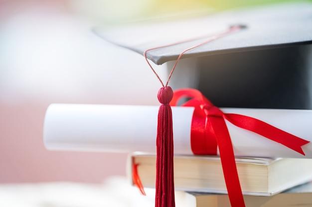 Крупным планом выборочный фокус выпускной шапки или ступки и диплома, положенного на стол