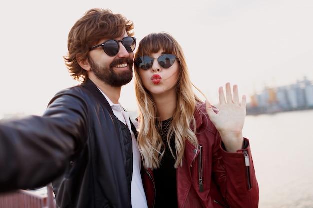 Закройте автопортрет милой игривой пары, весело проводящей романтические моменты вместе. в стильной кожаной куртке и солнечных очках.