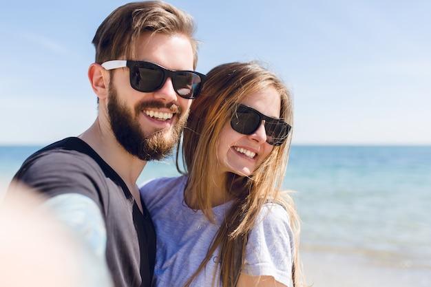 海の近くに立っている若いカップルのクローズアップの自画像