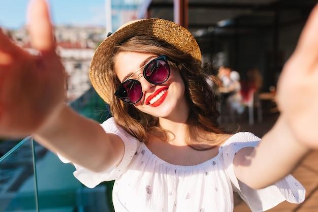 テラスで日光の上に立っている長い髪のかわいい女の子のクローズアップ自撮り写真。彼女は白いドレス、帽子、赤い口紅、サングラスを着ています。彼女は真剣に笑っています。