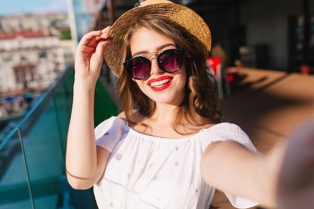 テラスで日光の上に立っている長い髪のかわいい女の子のクローズアップ自撮り写真。彼女は白いドレス、帽子、赤い口紅、サングラスを着ています。彼女は帽子に触れて笑っています。