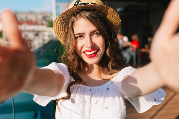 Close-up selfie-portrait of pretty girl with long hair standing on sunlight on terrace. she wears white dress, hat, red lipstick. she is holding phone with two hands and smiling.