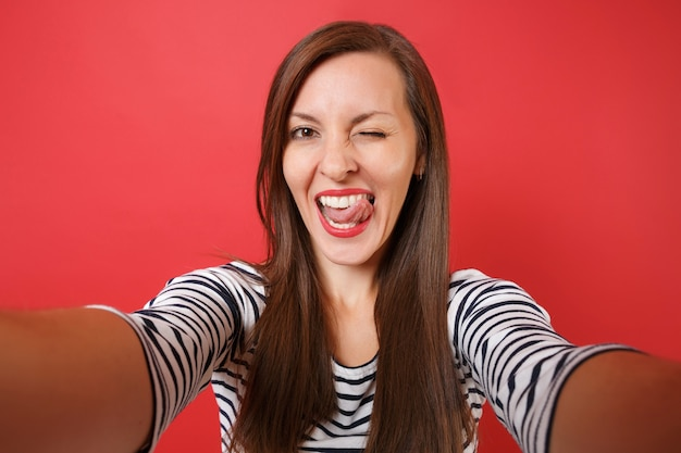 Close up selfie shot of cheerful young woman in casual striped clothes blinking, showing tongue