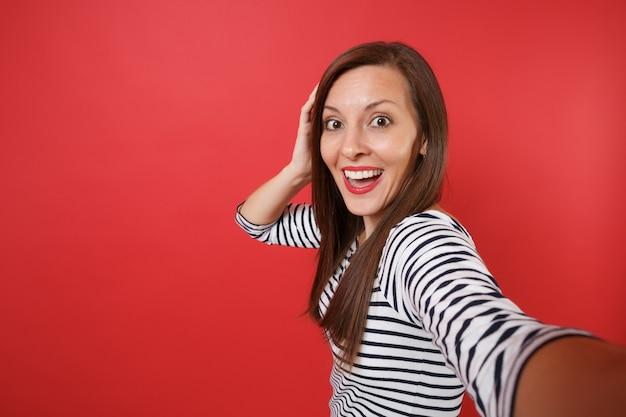 Primo piano selfie di una giovane donna eccitata in abiti a righe che tiene la bocca spalancata e sembra sorpresa