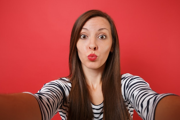 Primo piano selfie di una giovane donna divertente in abiti casual a righe che soffia baci manda un bacio d'aria