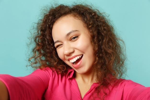 스튜디오의 파란색 청록색 벽 배경에 격리된 분홍색 캐주얼 옷을 입은 꽤 재미있는 아프리카 소녀를 깜박이는 셀카 사진을 클로즈업합니다. 사람들은 진심 어린 감정, 라이프 스타일 개념입니다. 복사 공간을 비웃습니다.