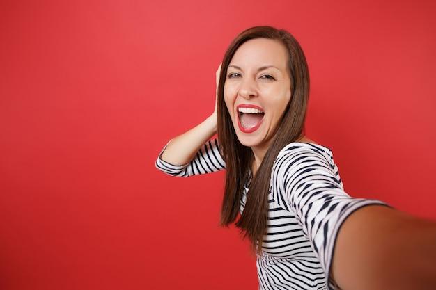 비명을 지르는 캐주얼 줄무늬 옷을 입고 웃긴 웃는 예쁜 젊은 여성의 셀카 샷을 닫습니다