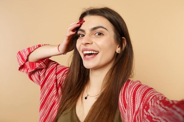 パステルベージュの背景で隔離の頭に手を置いて、カメラを探しているカジュアルな服を着て笑顔の若い女性のselfieショットを閉じます。人々の誠実な感情、ライフスタイルのコンセプト。コピースペースをモックアップします。