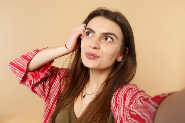 Primo piano selfie di una giovane donna pensierosa in abiti casual che guarda da parte, mettendo la mano sulla testa isolata su sfondo beige pastello. persone sincere emozioni, concetto di stile di vita. mock up copia spazio.