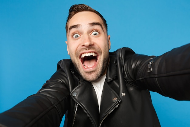 Close up selfie of stylish young unshaven man in black leather jacket white t-shirt looking camera isolated on blue wall background studio portrait. people sincere emotions concept. mock up copy space